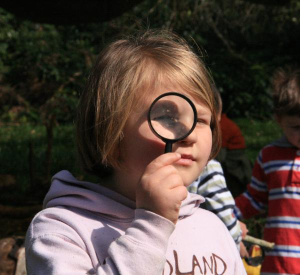 A child spying through a magnifying glass