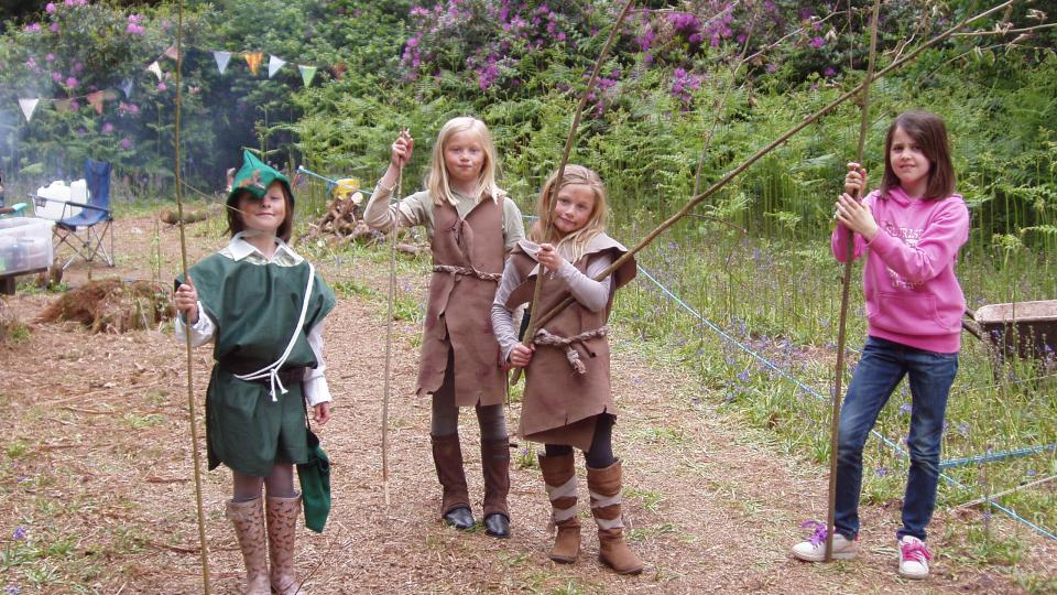 Children playing in costumes in the woods